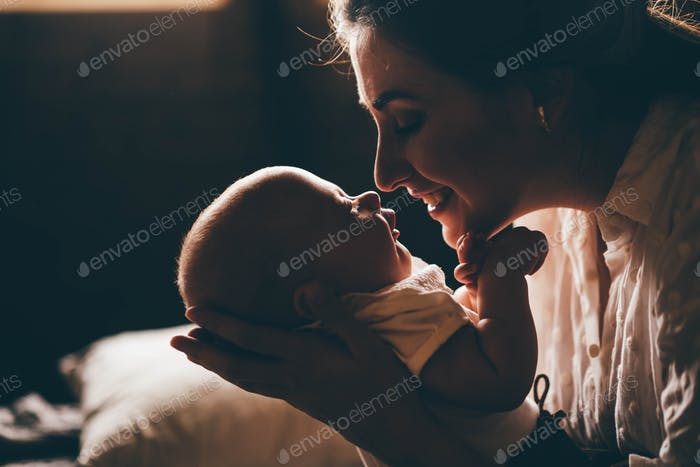 Young mother holding her newborn child. Mom nursing baby.