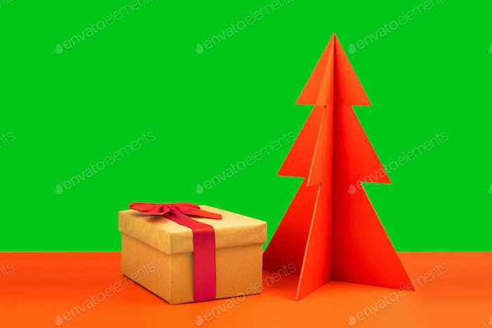 Gift box and envelope with red wooden Christmas tree on green background