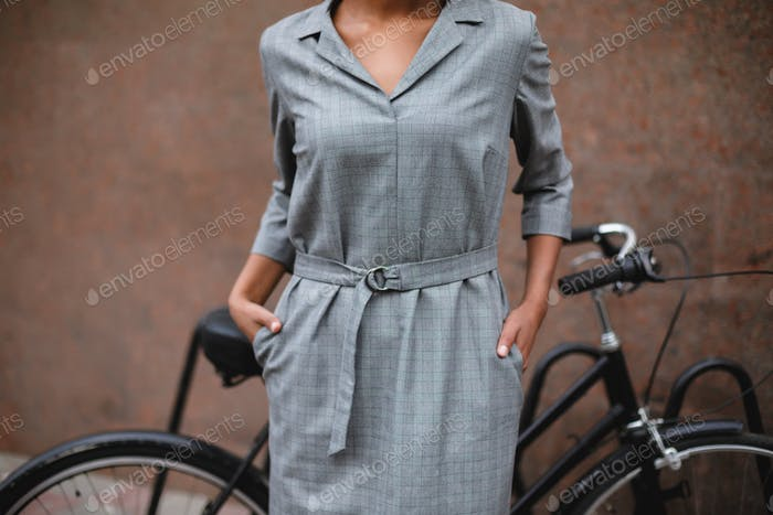 Close up photo of woman body in gray dress standing and holding hands in pockets