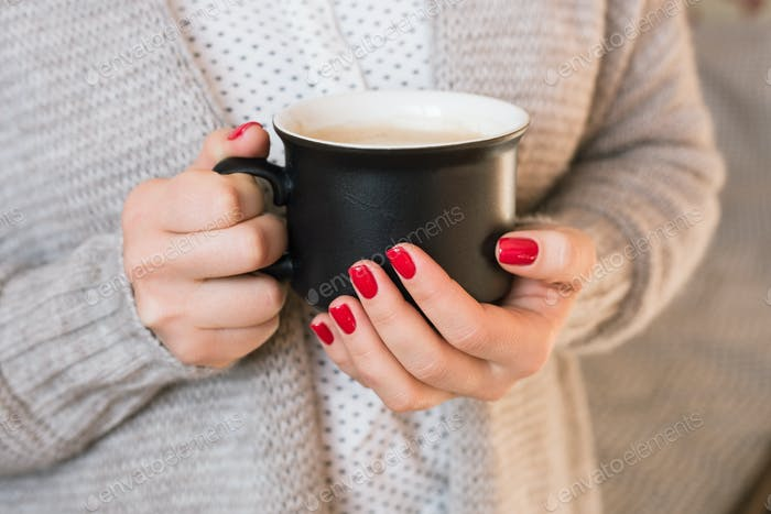 Beautiful young woman drinking coffee cappuccino, perfect red gel lacquer manicure.