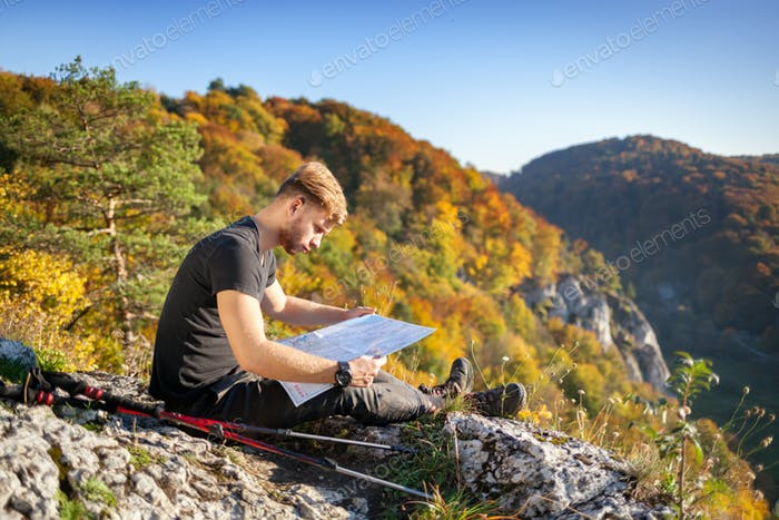 Traveler man after trekking sitting on rock looking at map and navigating