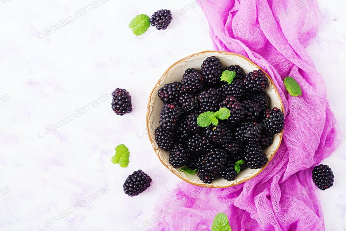 Summer berry on table. Healthy lifestyle concept, blackberries in bowl. Flat lay. Top view
