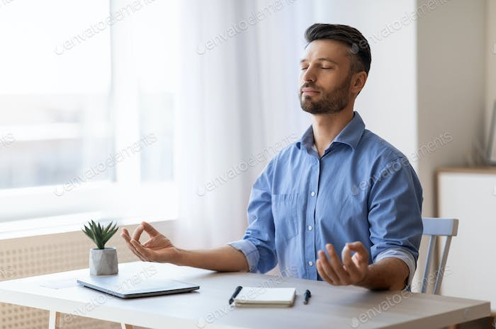 Calm Millennial Businessman Meditating At Workplace, Practicing Yoga In Office