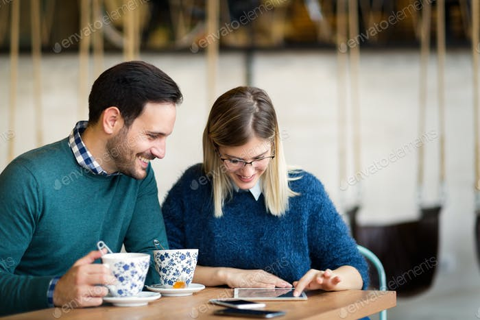 Young attractive man and beautiful woman on date looking on tablet