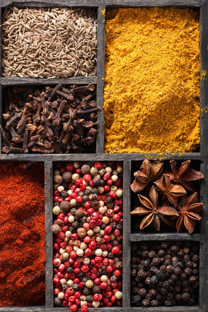 spices in box: pink and black pepper, ground paprika, curry, ani