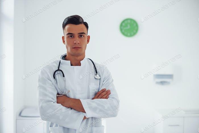 Mit gekreuzten Armen. Junge stilvolle männliche Arzt mit Stethoskop ist tagsüber in der Klinik