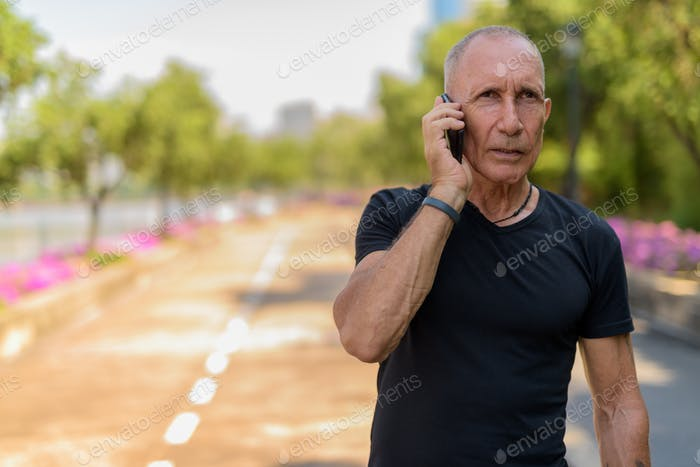 Bald senior tourist man thinking while talking on mobile phone o