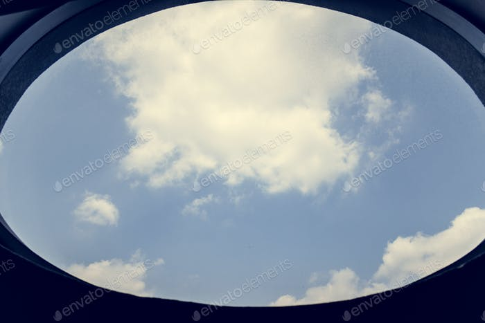 Cloudy blue sky through a window