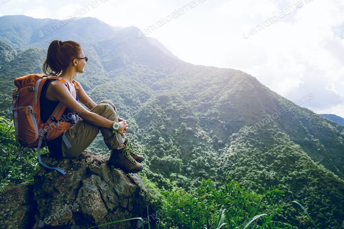 Woman hiker sit on mountain top enjoy the view