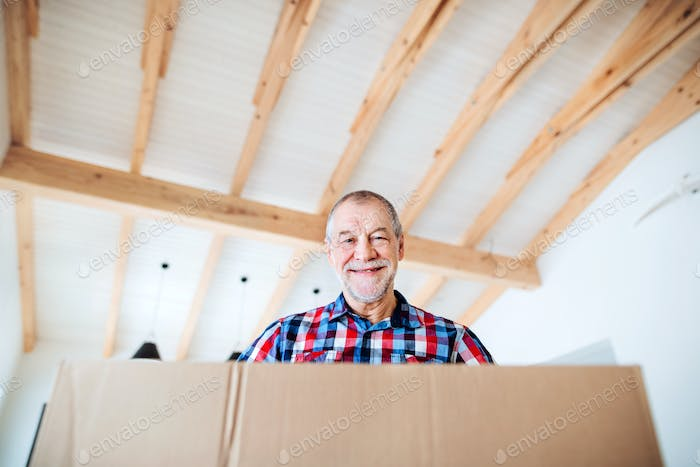 A low-angle portrait of senior man furnishing new house, a new home concept.