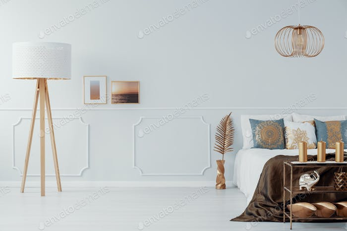 Light grey bedroom interior with gold accents in real photo with