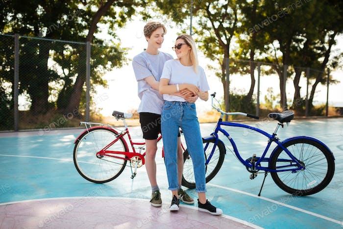 Porträt des jungen Paares glücklich auf einander suchen mit roten und blauen Fahrrädern auf Hintergrund