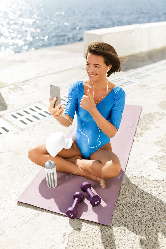 Smiling woman in swimsuit happily looking in cellphone showing thumb up gesture