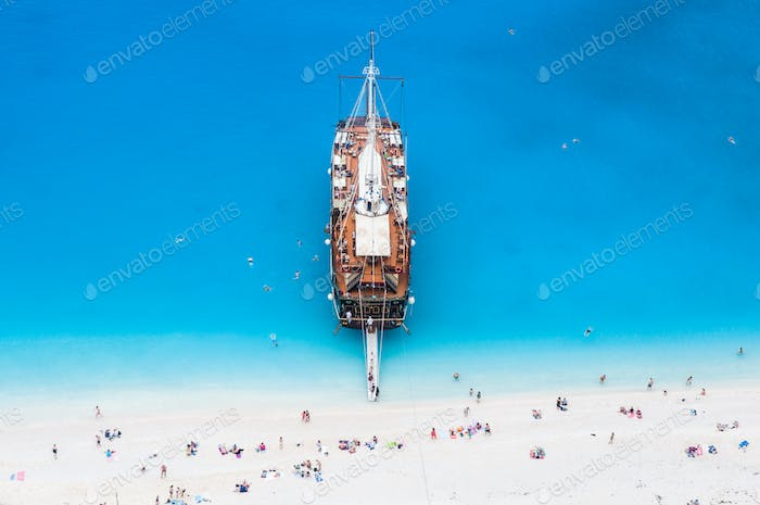 large sail cruise ship anchored at white sand beach, seen from above