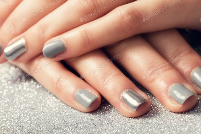 Woman's nails with shiny silver hybrid manicure