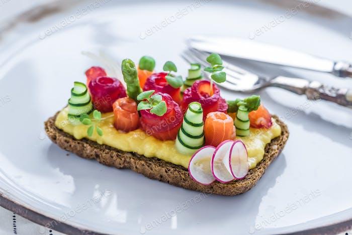 Dänischer Smorrebrod mit Gravlax und Omelett auf Roggenbrot
