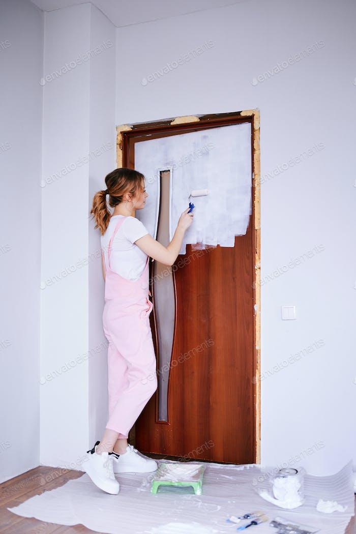 A girl in a pink work suit repaints an old door.