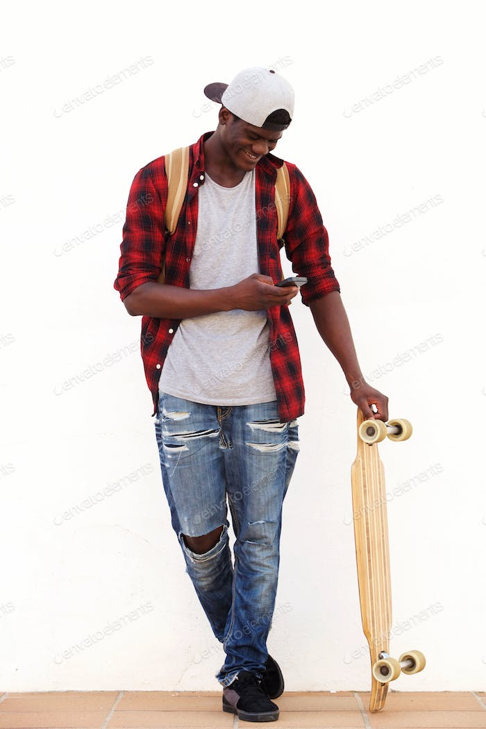 Full body happy young man with skateboard looking at cell phone and smiling