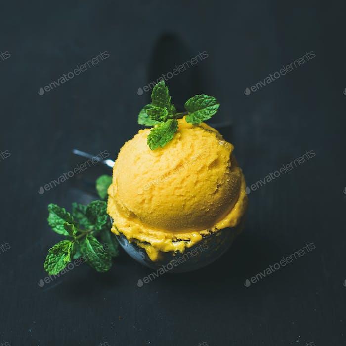 Refreshing Mango sorbet ice-cream scoop in scooper, square crop