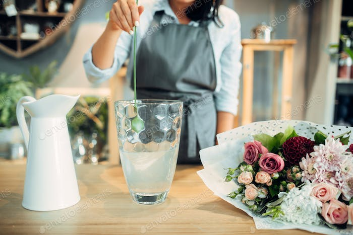 Florist adds fertilizer to the water for flowers