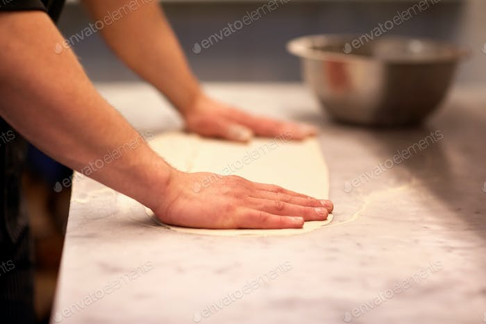 chef hands preparing dough on table at kitchen