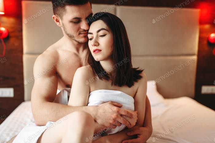 Couple hugging on big white bed after intimacy