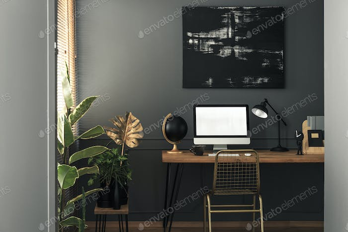 Painting above desk with desktop computer and lamp in grey and g