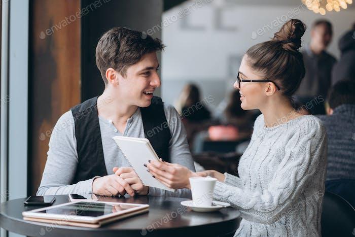 Chico y chica en una reunión en un café