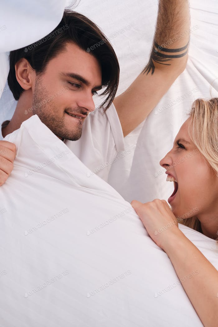 Young man and attractive emotional blond woman fighting for pillow lying under blanket