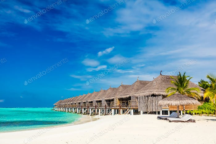 Tropical beach with straw cabins on Maldives.