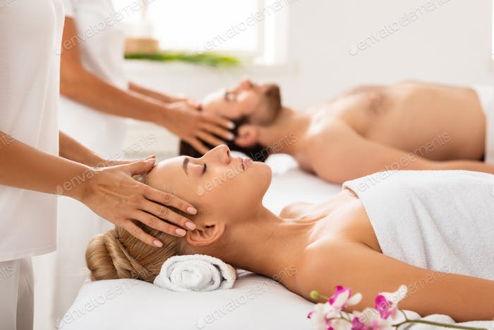 Couple Receiving Head Massage Relaxing With Eyes Closed Indoors