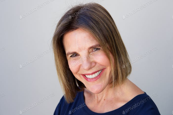 smiling woman against gray wall