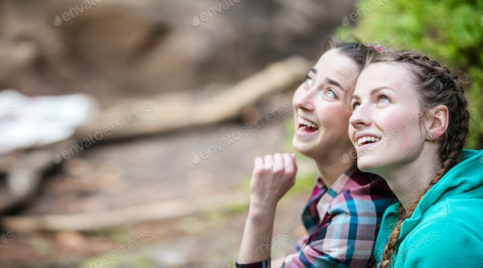 Two young women looking up at something and smiling