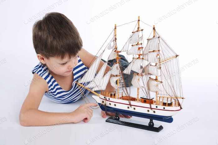 little boy with ship on white