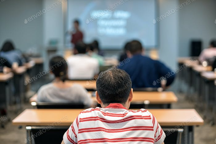 Rear view of Audience listening the asian speaker on the stage in the meeting room or conference