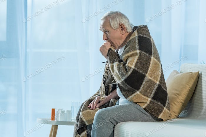 Senior chilled man covered in plaid coughs while sitting sofa in room with medications on table