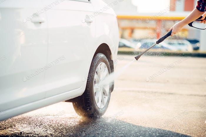 Female person cleans car wheels with water gun