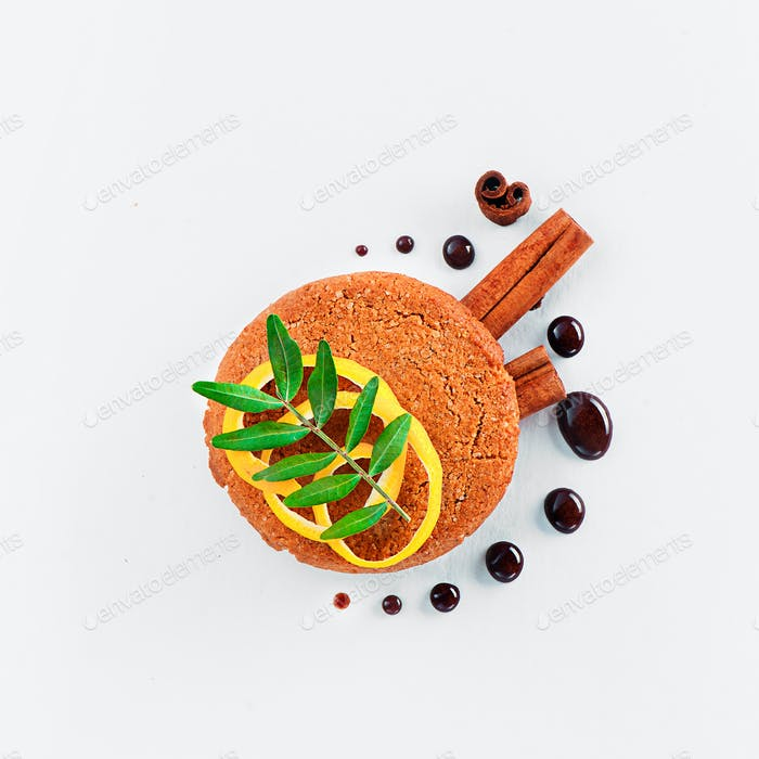 Cookie decorated with lemon zest, chocolate drops, cinnamon, and green leaves on a white background
