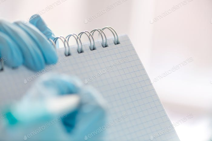 Female hand in a medical glove holds a tablet for writing and a pen