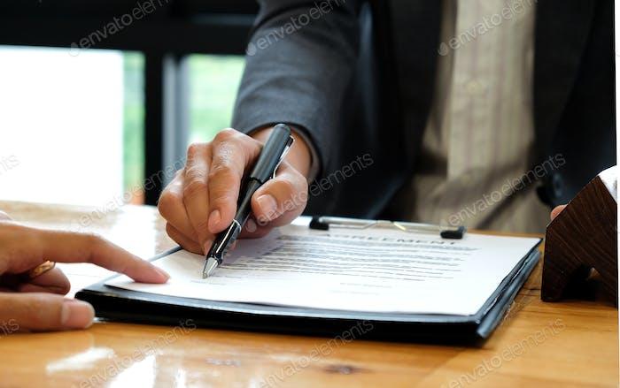 Unternehmer, die das Haus verkaufen, das beim Unterzeichnen des Kaufvertrags zeigt.