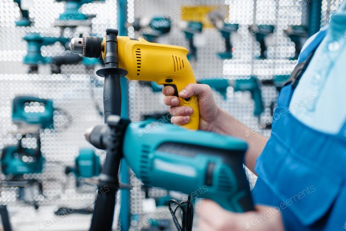 Worker holds two electric drills in tool store