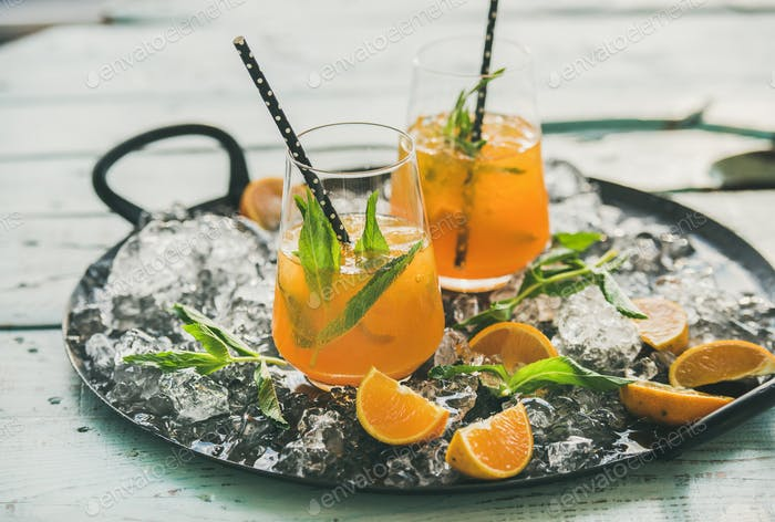 Refreshing cold alcoholic summer cocktail with orange on tray