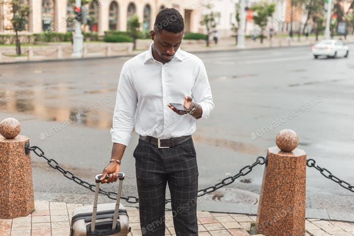 Afro businessman with luggage use phone to hire a taxi. Black man in business trip