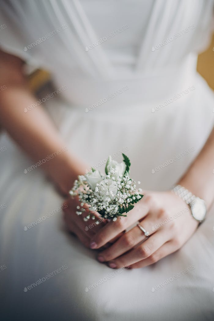 Stylish bride holding in hands boutonniere with white roses and gypsophila