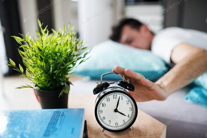 Young tired man hitting alarm clock in bed at home, waking up in morning
