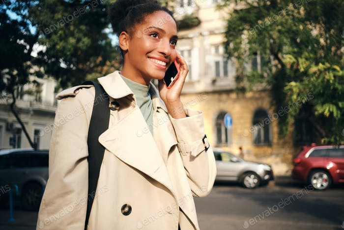 Cheerful African American girl in stylish trench coat happily talking on cellphone on city street