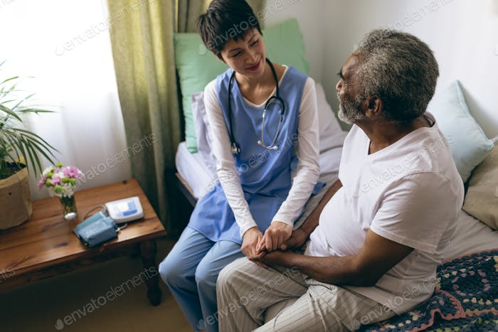 Female doctor and senior patient are holding hands at retirement home