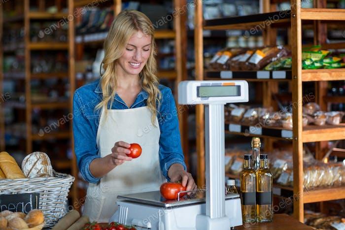 Weibliche Mitarbeiter Gewichtung Gemüse auf Skala