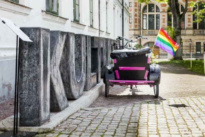 Regenbogenflagge auf Dreiradwagen durch Zeichen