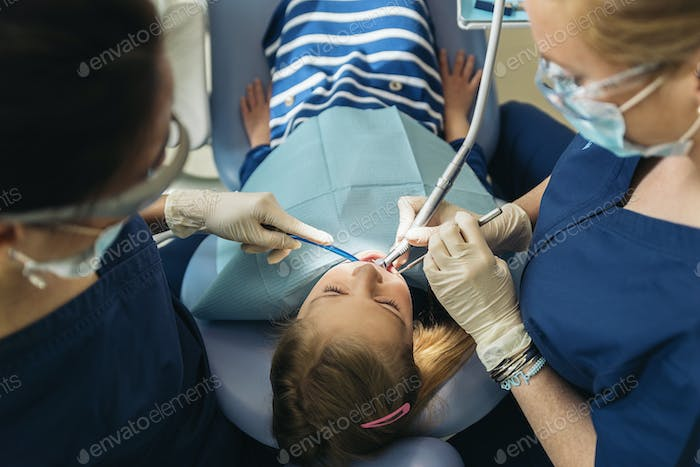 Dentists with a patient during a dental intervention to girl.